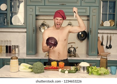 Angry man chef with sexy torso stab knife at purple cabbage in kitchen. Vegetarian, food, health, diet, dieting, cooking concept.