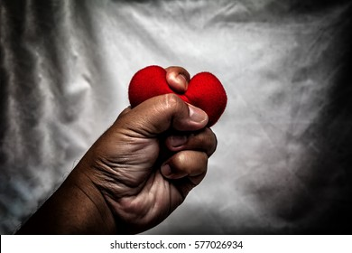 angry man crushing red heart in hand., unrequited love., love concept for valentine's day., in dark tone.