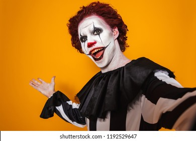 Angry man dressed in scary clown Halloween costume isolated over yellow background, taking a selfie