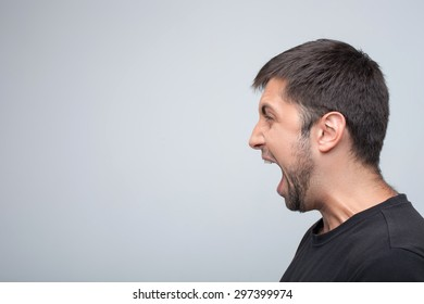 Angry man is evincing his aggression. He is standing in profile and shouting. Isolated on grey background and copy space in left side