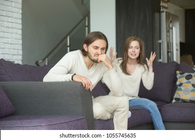 Angry man feels indignant about hysterical girlfriend complaining of bad relationships, frustrated annoyed husband sitting on sofa ignoring wife blaming shouting at him, couple disagreement concept