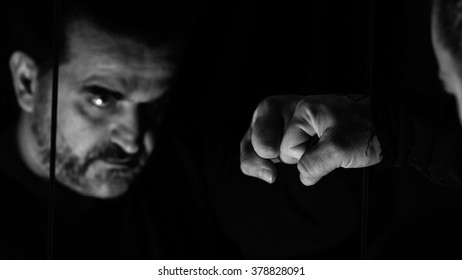 Angry man fist punching mirror and his reflection, monochromatic image