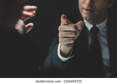 Angry man in formal business suit pointing hand to somesone he talking to in dark interrogation room