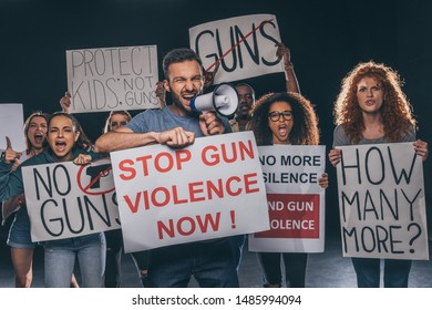 angry man holding placard with stop gun violence now lettering and screaming in megaphone near multicultural people on black