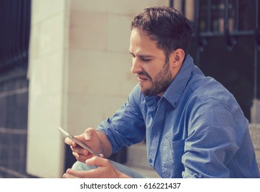 Angry man looking at his mobile phone sitting on steps outside apartment complex