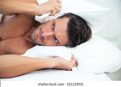 Angry man lying in the bed with pillow on head at home