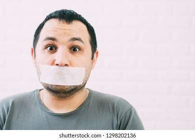 Angry man mouth covered by masking tape