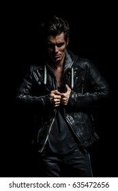 angry man pulling his leather jacket's collar on black studio background