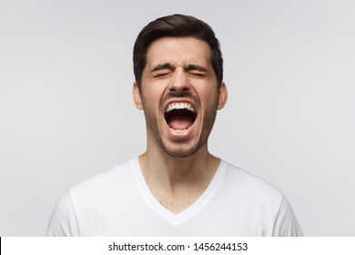 Angry man, rage concept. Close-up portrait of screaming with closed eyes crazy young man isolated, on gray background