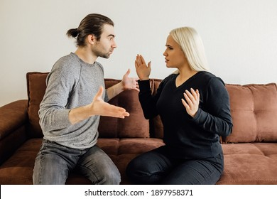 Angry man shouted at his wife, who covered her ears with her hands. family crisis conflict concept