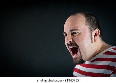 Angry man shouting against black background.