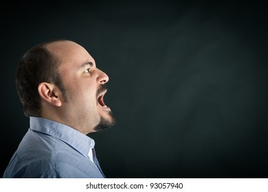 Angry man shouting against black background with room for your text. Conceptual image.