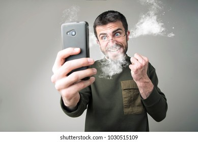 Angry man shouting at his cell phone, enraged with the bad service, burning with rage
