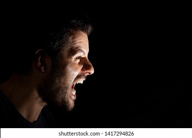 Angry man shouting out loud isolated on black background.