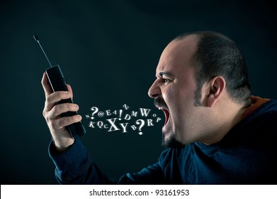 Angry man shouting at the phone against black background with letters out of his mouth.