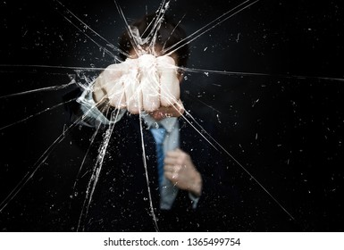 Angry Man in suit and tie punch and breaking glass his fist on dark background