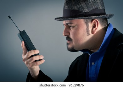 Angry man talking at the phone against grey background.