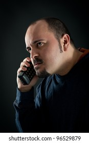 Angry man talking at the phone against black background.