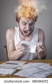 Angry man tearing bills apart, stressed and outraged, his head's on fire