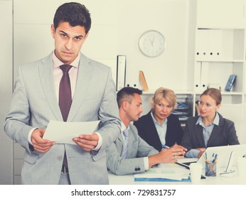 Angry manager standing in office dissatisfied with teamwork of colleagues