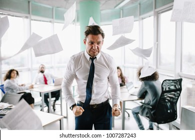 Angry manager in white shirt standing angrily at his desk. Throwing papers.