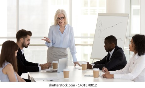 Angry mature businesswoman, middle-aged boss scold, blame employees for bad work results, holding business briefing, lecturing office workers team, subordinates for business failure at company meeting