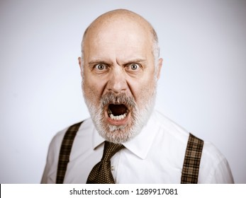 Angry mature man posing ans shouting at the camera, he is aggressive and threatening