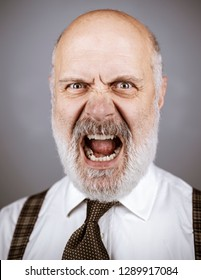 Angry mature man posing and shouting at the camera, he is aggressive and threatening