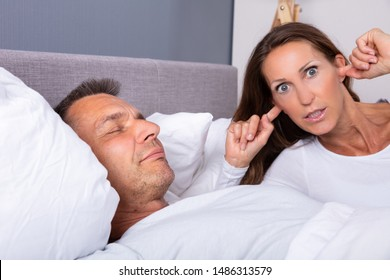 Angry Mature Woman Plugging Ear With Finger While Lying Near Snoring Husband In Bed