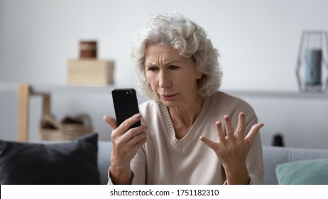 Angry mature woman sit on couch at home feel frustrated by slow internet connection on cellphone, mad elderly female confused stressed by smartphone operation problems, virus or spam messages