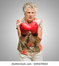 Angry Mature Woman Wearing Boxing Gloves On Grey Background