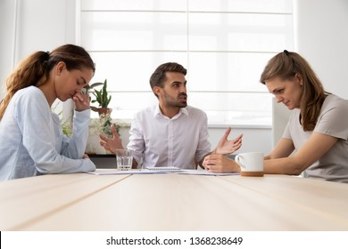 Angry mean male boss shouting criticizing stressed sad female employees scolding for bad work incompetence, business man bullying humiliating women at workplace, gender discrimination at work concept