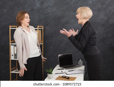 Angry middle aged boss yelling at young employee, she is stressed and feeling frustrated. Bullying boss and mobbing concept