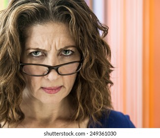Angry middle aged female teacher frowning over her glasses.