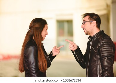 Angry millennial couple arguing and blaming each other of problem, frustrated about their relationship.