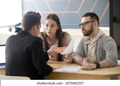 Angry millennial couple complaining having claims about bad contract terms disputing at meeting with lawyer, deceived dissatisfied customers demanding compensation, legal fight and fraud concept