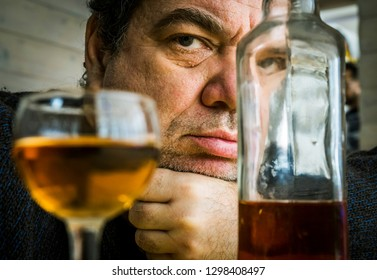 Angry moody drunk male alcoholic at the table with a bottle and glass