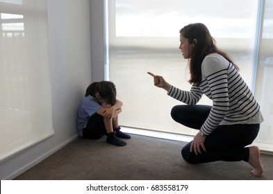 Angry mother (age 30-35) angry with her bad daughter (age 07) sitting in the corner on the floor. Family life concept. Real people. Copy space