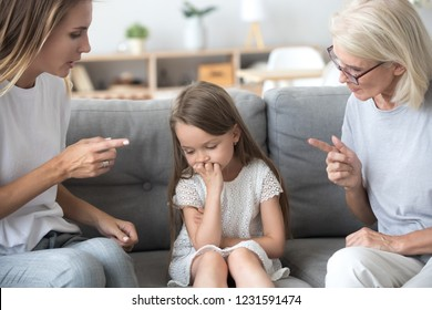 Angry mother and grandmother scolding lecturing upset kid girl together, strict young mom and old grandma talking to child reprimanding  demanding discipline, three generations upbringing concept