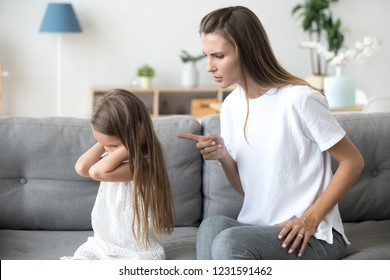 Angry mother scolding lecturing stubborn kid closing ears not listening to mom, strict mum talking to rebellious child demanding discipline from preschool girl ignoring rebuke family conflict concept