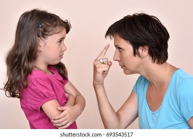 Angry mother scolding a scared daughter
