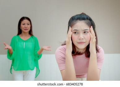 Angry mother stands behind her daughter complaining something