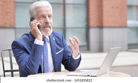 Angry Old Businessman Talking on Phone