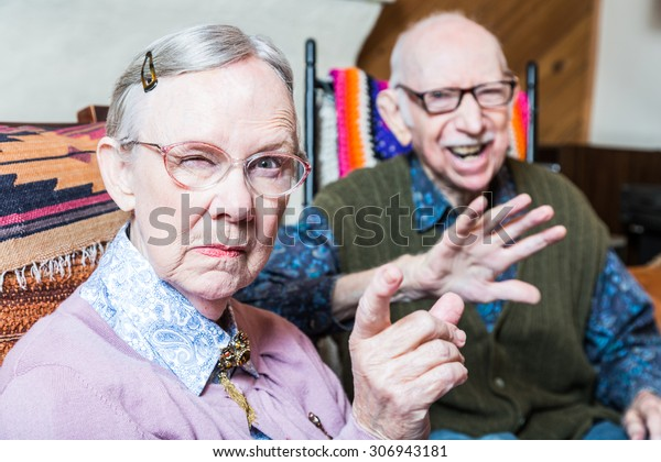 Angry old couple sitting in living room woman pointing