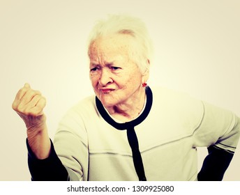 Angry old woman making a fist in studio