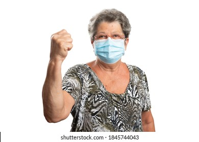 Angry old woman showing fist as fight aggressive gesture wearing sars covid influenza flu virus pandemic protection medical or surgical disposable mask to prevent contamination isolated on white