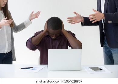 Angry overwhelmed african businessman frustrated with discrimination at work, hates stressful job, feels headache or closing ears to avoid annoying people noise, nervous breakdown or burnout concept