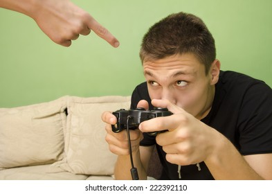 Angry Parent forbids his kid to play video game. Kid hiding behind controller