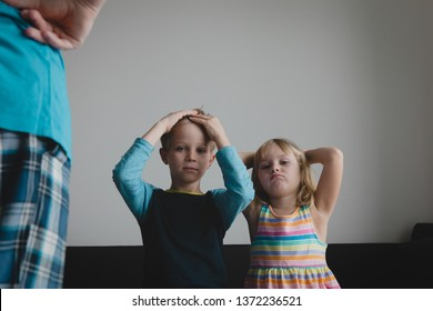 angry parent looking at ashamed and exhausted kids