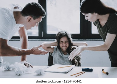 Angry Parents Yells at Girl while Homework Doing. Frowing Caucasian Scared Child Wears Gray T-Shirt Sits at Desk in Front of Window Closes Ears and Eyes with Hands when Parents Scolding